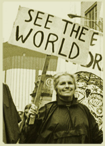 "Photo of Grace Paley at a New York City demonstration, carrying a sign that says ""See the World""."